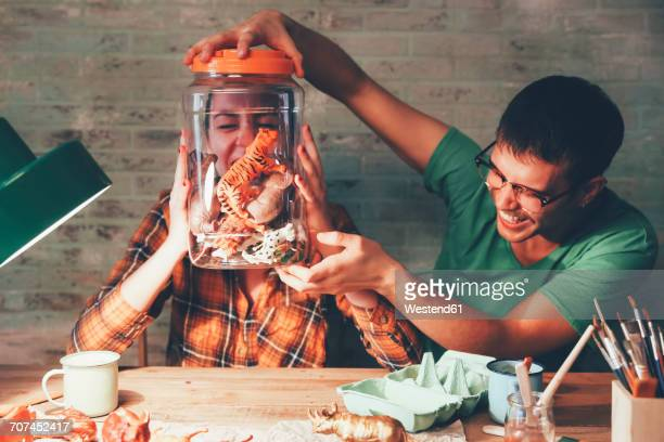 young couple having fun with animal figurines in jar - freaky couples stock photos and pictures