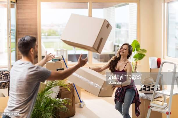 Junge Paare, die Spaß mit Kartons beim Umzug in neue Wohnung.