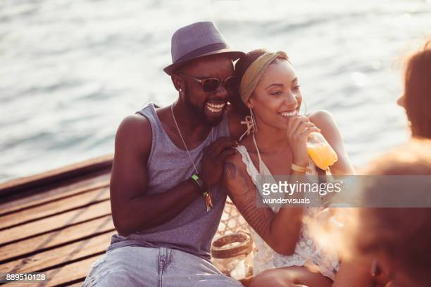 Young couple having fun with friends on jetty in summer