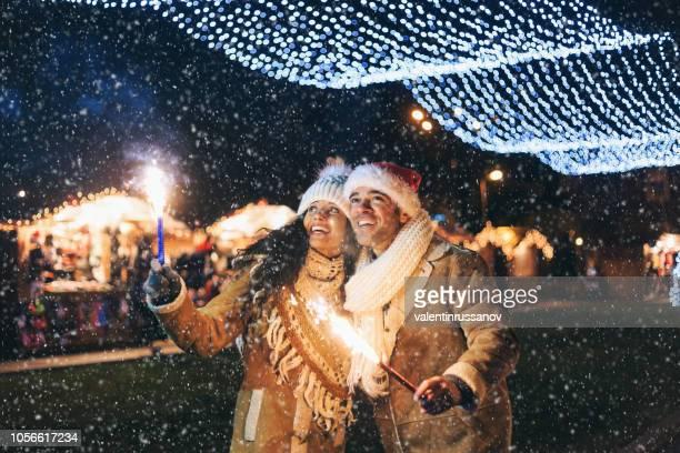 casal jovem se divertindo com espumantes velas à noite - mercado natalino - fotografias e filmes do acervo