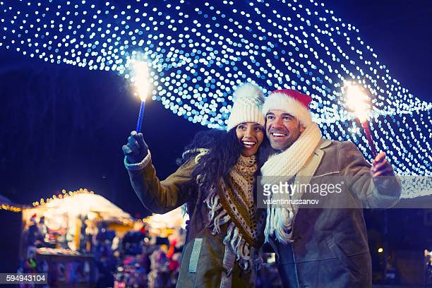 Young couple having fun with sparkling candles at night