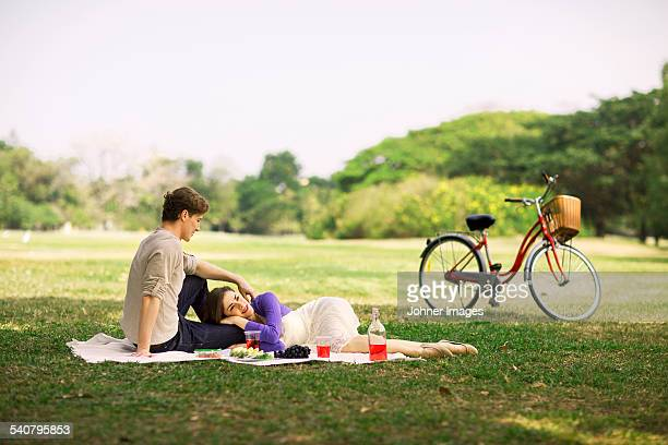 young couple having picnic - 腹ばい ストックフォトと画像