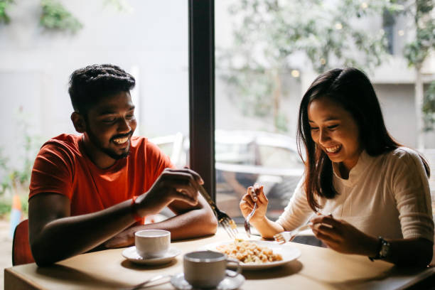 young couple having pizza together - couples romance stock pictures, royalty-free photos & images