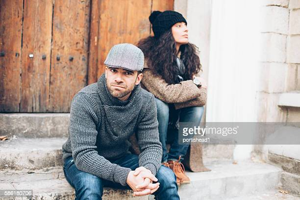 Young couple having problems and sitting in doorway outside