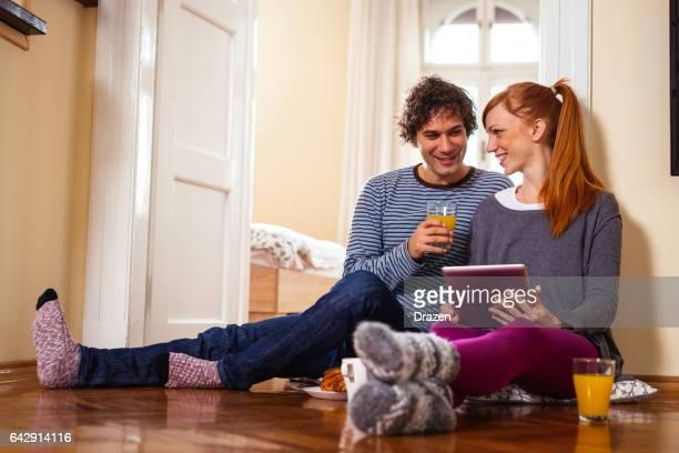 Young couple having snack at home, using internet for developing of new business ideas