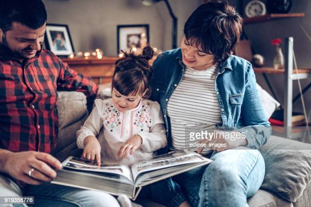 young couple having some family time with daughter - photo album stock photos and pictures