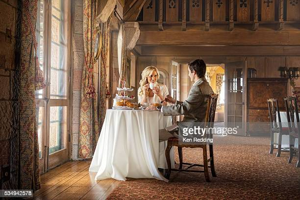 Young couple having tea at small table in front of large French doors in castle