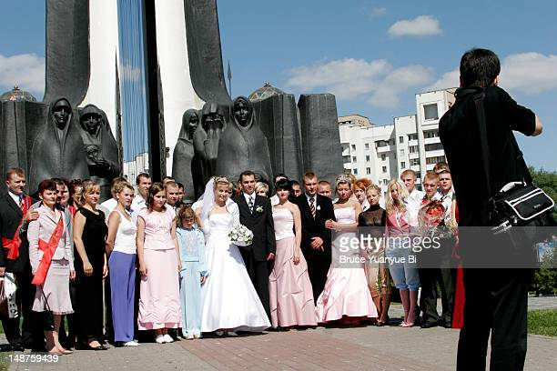 Young couple having their wedding photos taken with guests on Island of Tears (Afghan war memorial).
