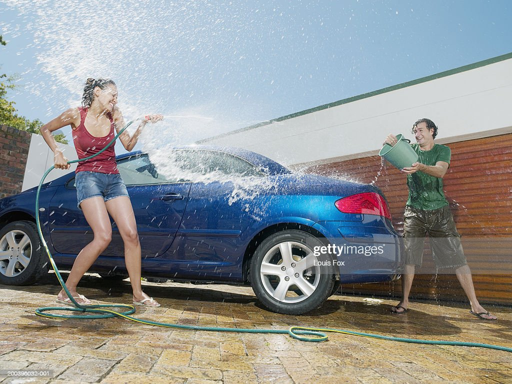 Young couple having water fight by car : Stock Photo