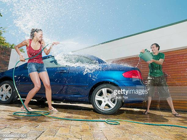 young couple having water fight by car - red tube top stock photos and pictures