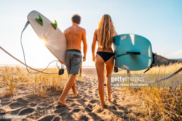 young couple heading out for surfing. - bondi beach stock pictures, royalty-free photos & images