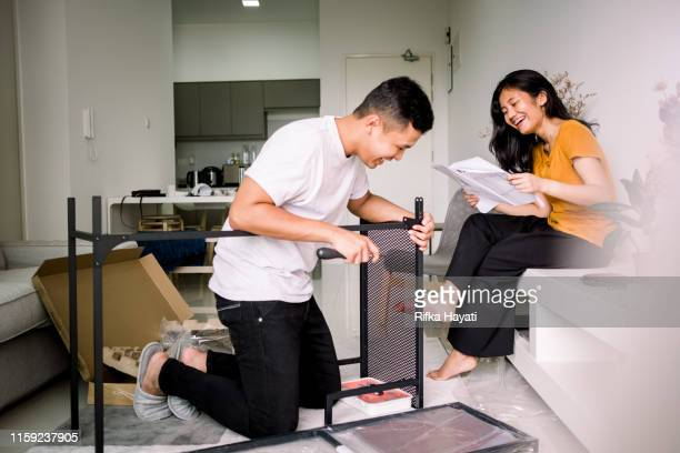 young couple helping each other assembling table - furniture stock pictures, royalty-free photos & images