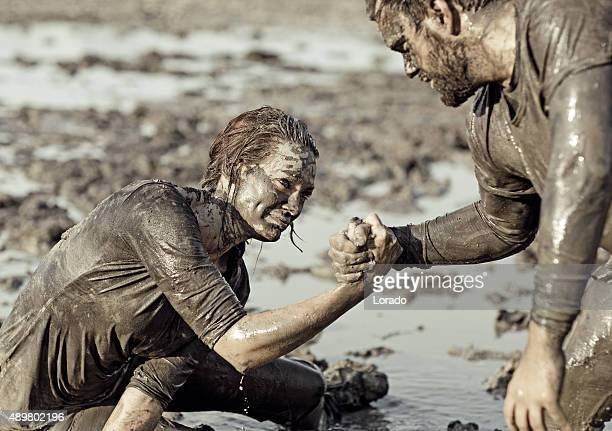 young couple helping each other during a mud run - obstacle course stock photos and pictures