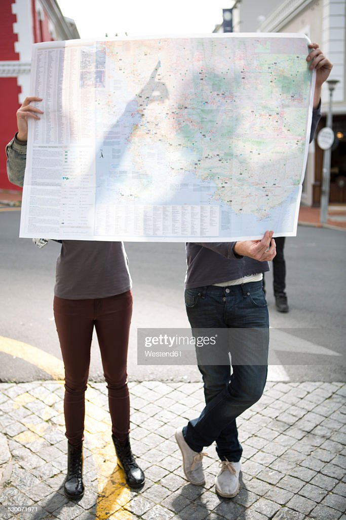 Young couple hiding behind a city map : Stock-Foto