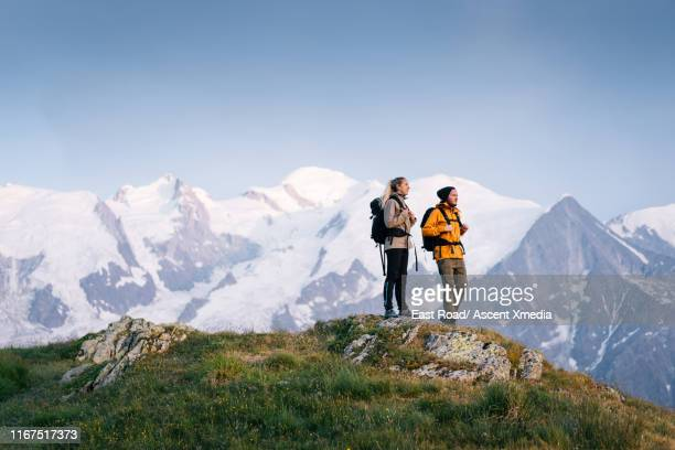 young couple hike along high mountain passes in the alpine - haute savoie stock photos and pictures