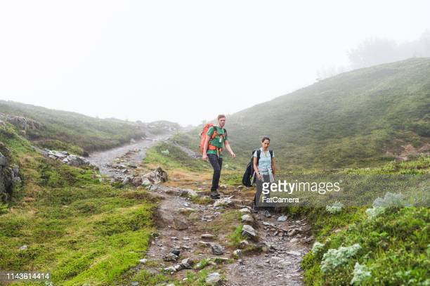 a young couple hike down a foggy glacier with their backpacks - kenai mountains stock pictures, royalty-free photos & images