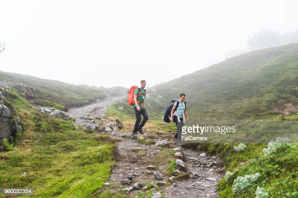 A young couple hike down a foggy glacier with their backpacks