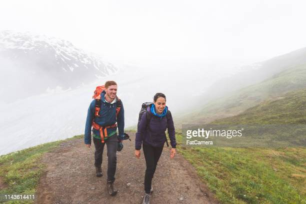 a young couple hike up a foggy glacier with their backpacks - kenai mountains stock pictures, royalty-free photos & images
