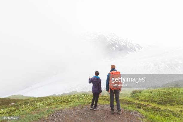 A young couple hike up a foggy glacier with their backpacks