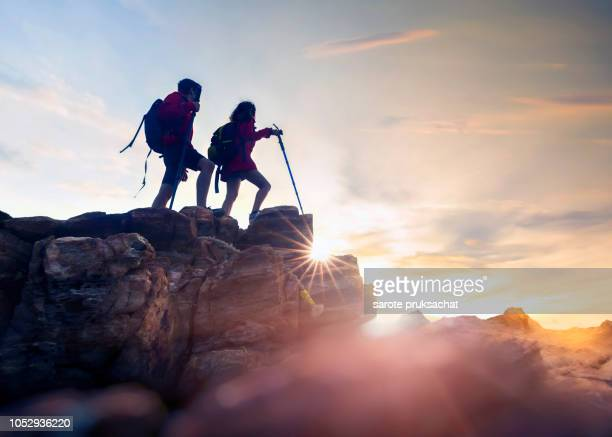 young couple hikers climbing up hike on the peak of rocks mountain  during sunset - 立ち向かう ストックフォトと画像