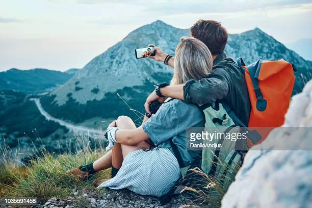 junges paar wanderer nehmen eine selfie oben auf dem berg - hoch position stock-fotos und bilder