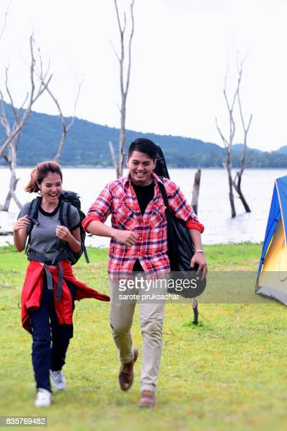 Young couple hikers with backpack holding in the countryside .Camp Forest Adventure Travel Remote Relax Concept .