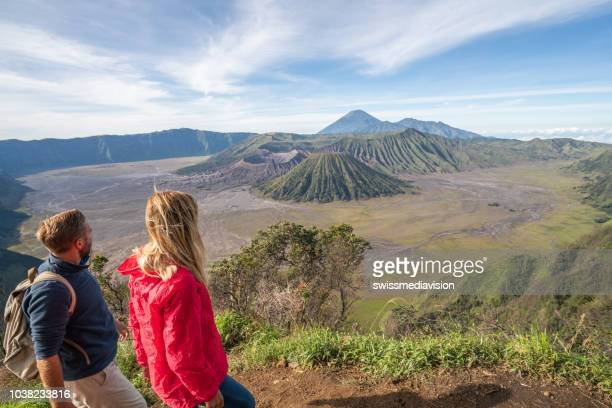 young couple hiking contemplate volcanic landscape from top of hill looking at bromo volcanoes- people travel adventure concept - bromo crater stock pictures, royalty-free photos & images