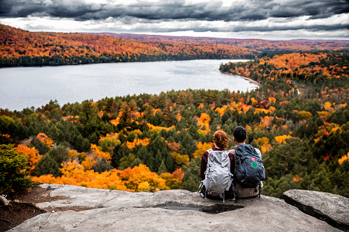 Young couple hiking in mountain and relaxing looking at view 621242410