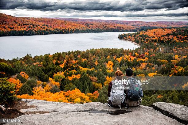 young couple hiking in mountain and relaxing looking at view - herfst stockfoto's en -beelden