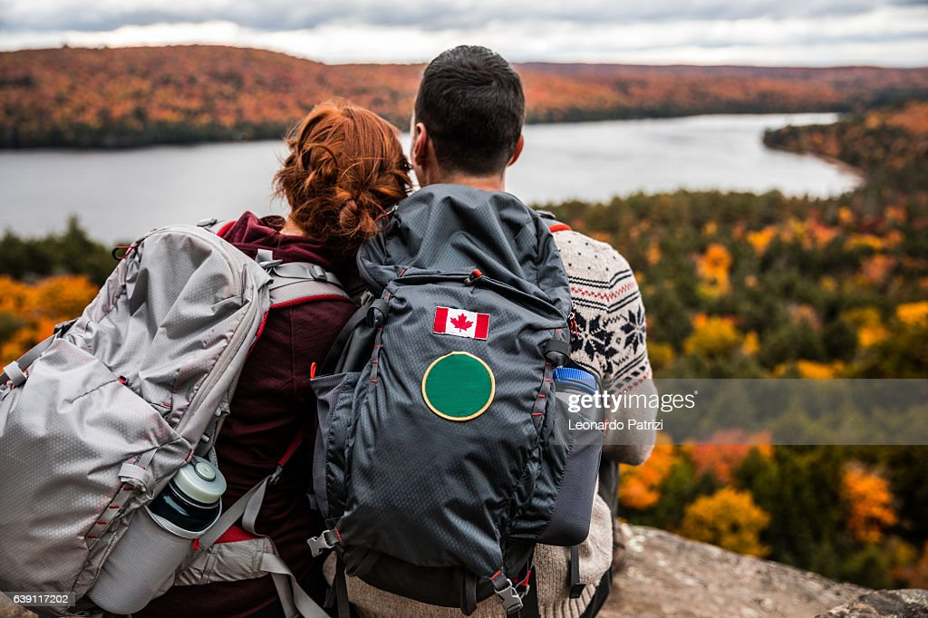 Young couple hiking in mountain and relaxing looking at view : Stock Photo