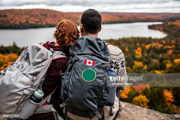 young couple hiking in mountain and relaxing looking at view - カナダ ストックフォトと画像