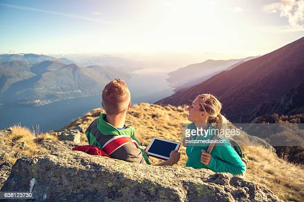 Young couple hiking look at digital map on tablet