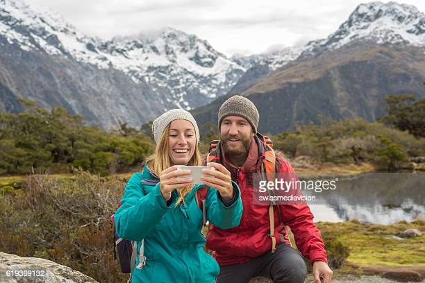 Young couple hiking take selfie portrait with mountain scenery
