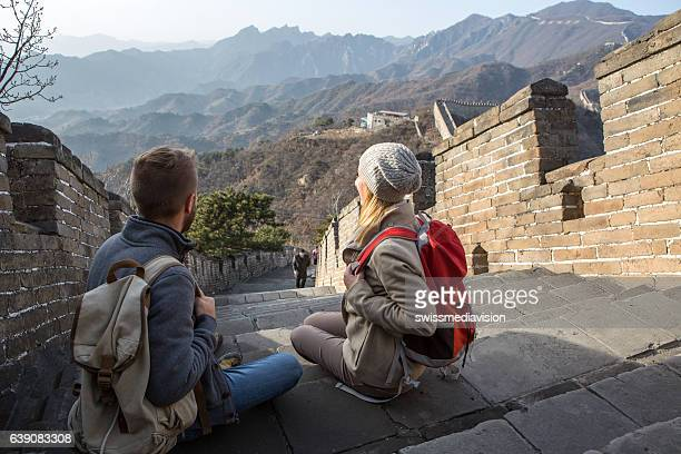 Young couple hiking the Great Wall looking at spectacular landscape-China