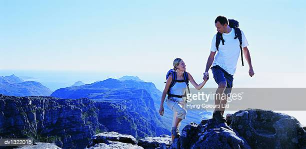 Young Couple Hking and Holding Hands on Mountain Top