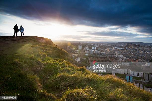 A young couple hold hands in front of the view of the City of Edinburgh from Salisbury Crags