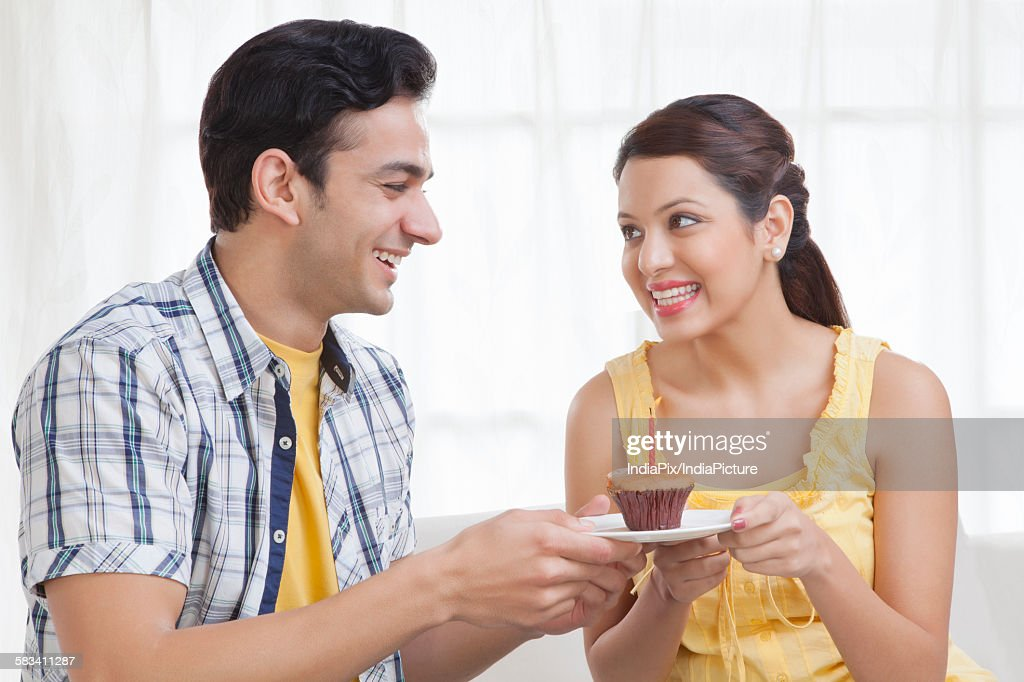 Young couple holding a plate with a cupcake : Stock Photo