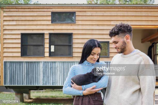 young couple holding a puppy outside their tiny house - young animal stock pictures, royalty-free photos & images