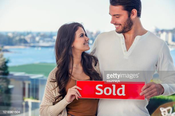 Young couple holding a sold sign in a luxury home.