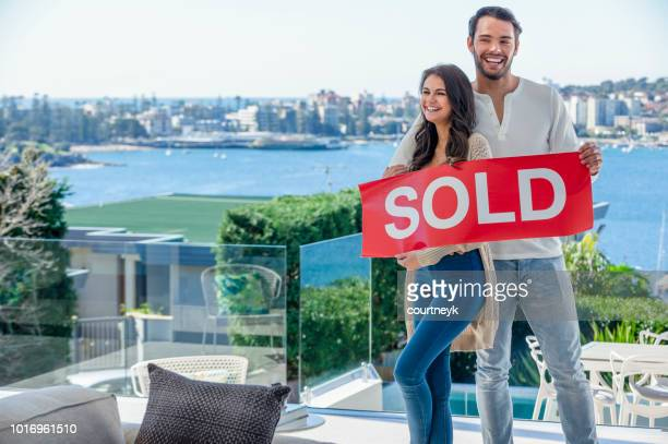 young couple holding a sold sign in a luxury home. - real estate stock pictures, royalty-free photos & images