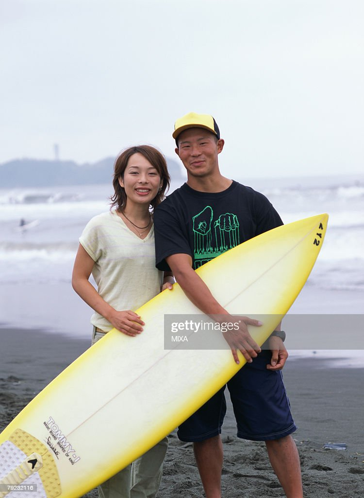 Young couple holding a surf board : Stock Photo