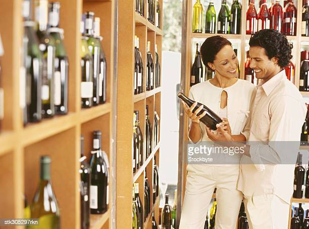 young couple holding a wine bottle in a store