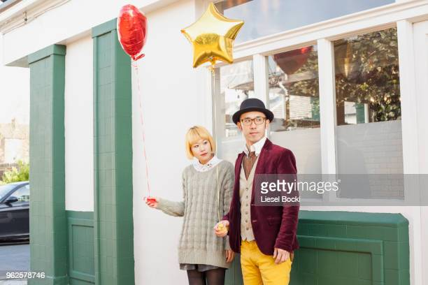 young couple holding balloons and looking away while standing against window - somente japonês - fotografias e filmes do acervo
