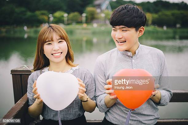 Young couple holding balloons in summer park