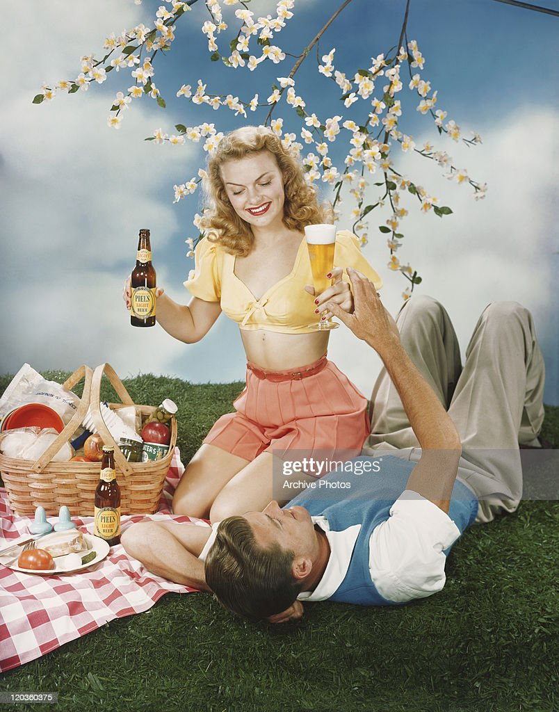 young couple holding beer and having fun at picnic ストックフォト