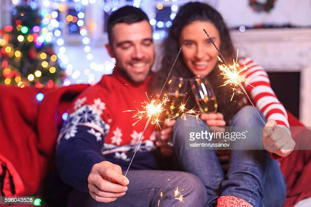 young couple holding bengal fire and drinking champagne at home - bengal new year stock photos and pictures