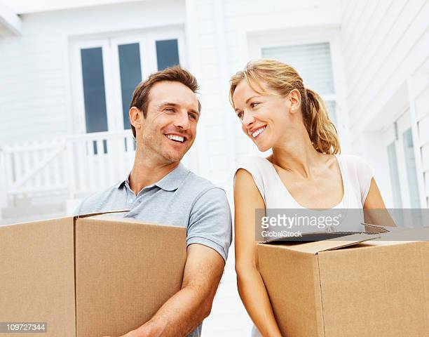 Young couple holding cardboard box