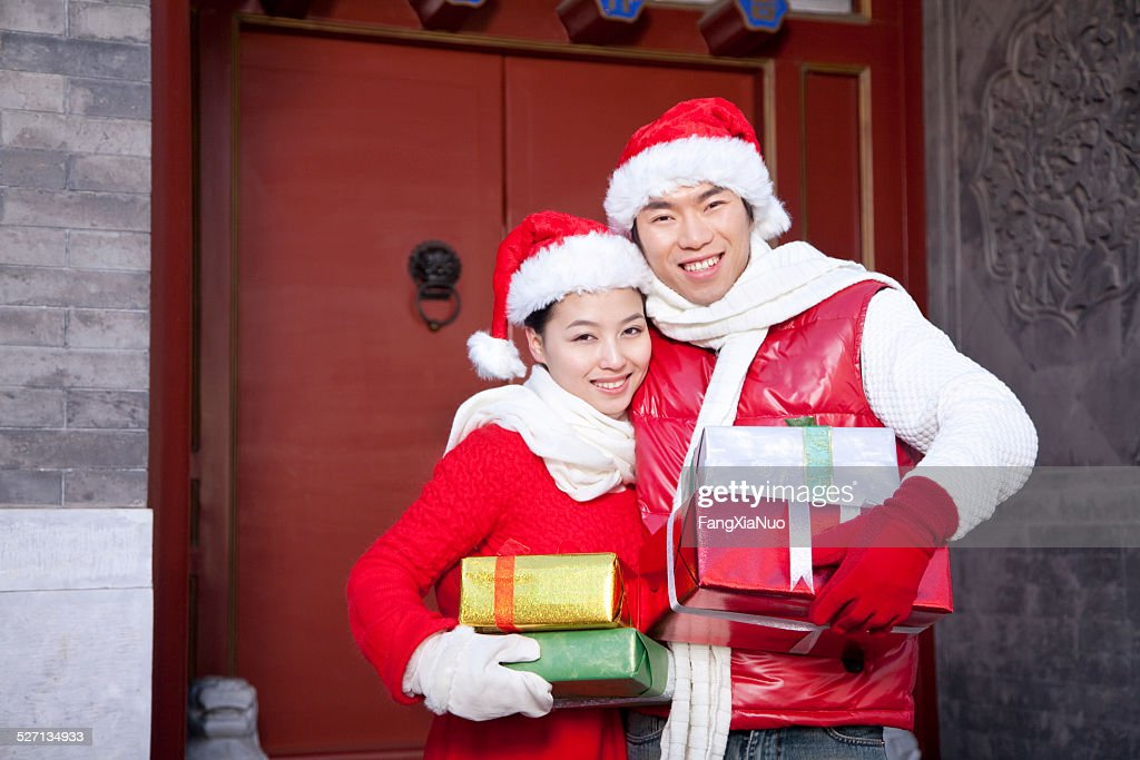 young couple holding christmas gifts stock photo
