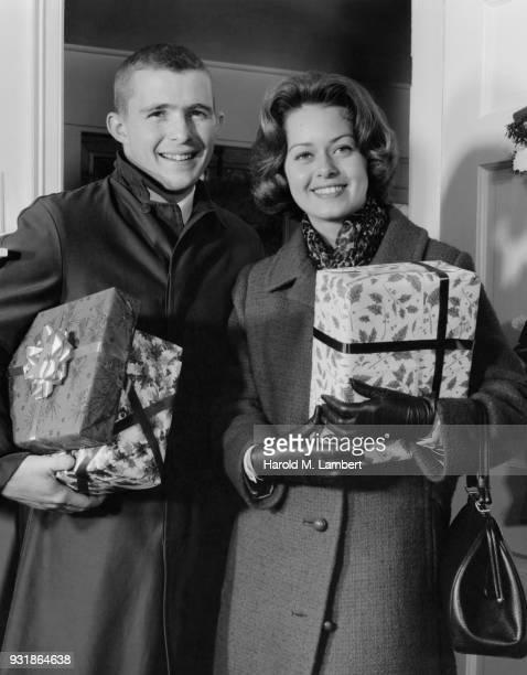 young couple holding christmas gifts - heterosexuelles paar stock-fotos und bilder