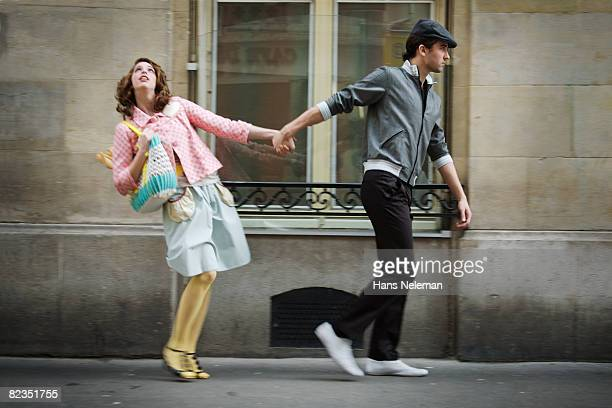 Young couple holding each other's hands and walking on the street, Paris, France